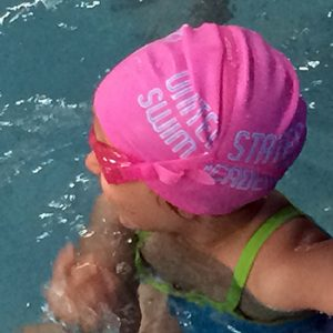 Custom swim cap for swimming academy. Pink. Logo printed on both sides